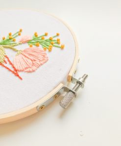 Floral Embroidery displayed in a 5-inch bamboo embroidery hoop. Close up of the screw mechanism.